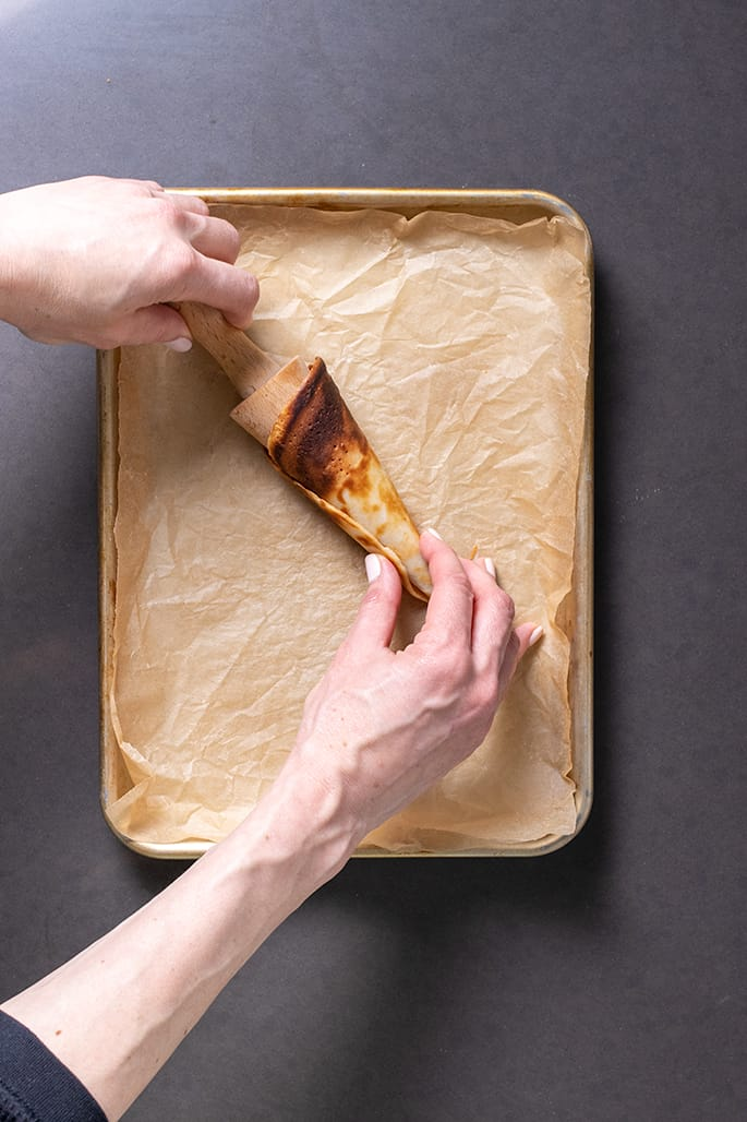 Hands rolling cone pancake onto wooden cone with handle
