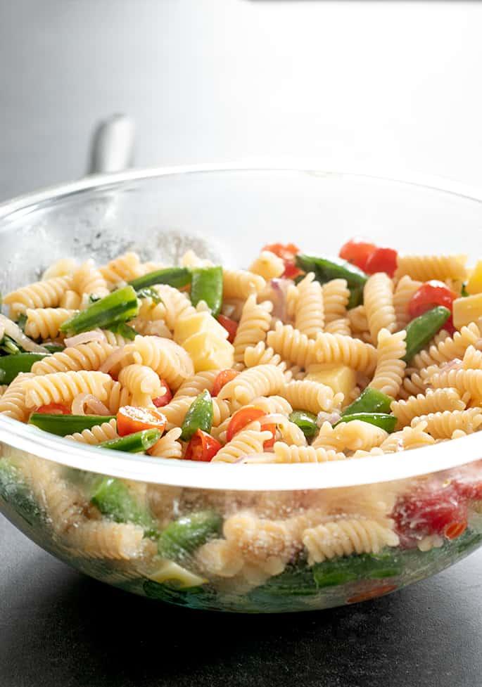 Warm gluten free pasta salad in serving bowl.