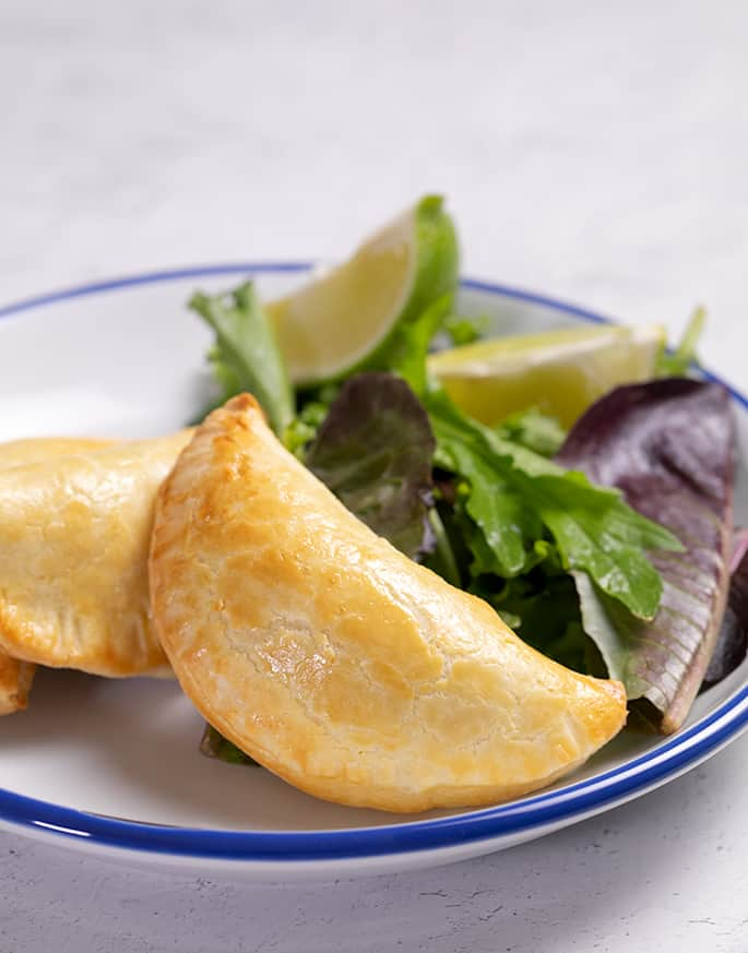 Three empanadas on a white plate with greens and a lime wedge