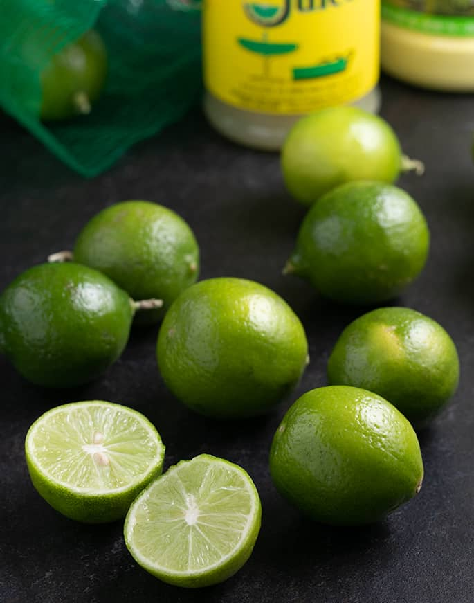 Key limes on black table with one sliced in half and bottles in background