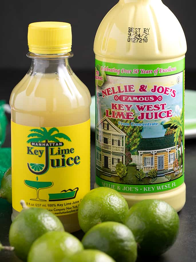 Key limes on table with two brands of bottled key lime juice