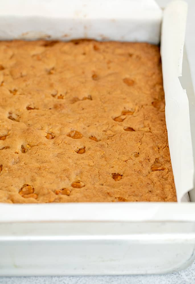 Magic blondies baked in square metal pan with white paper liner