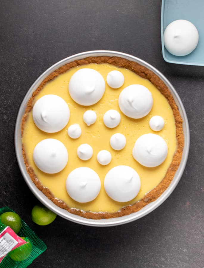 Overhead image of whole key lime pie with meringues and key limes on table