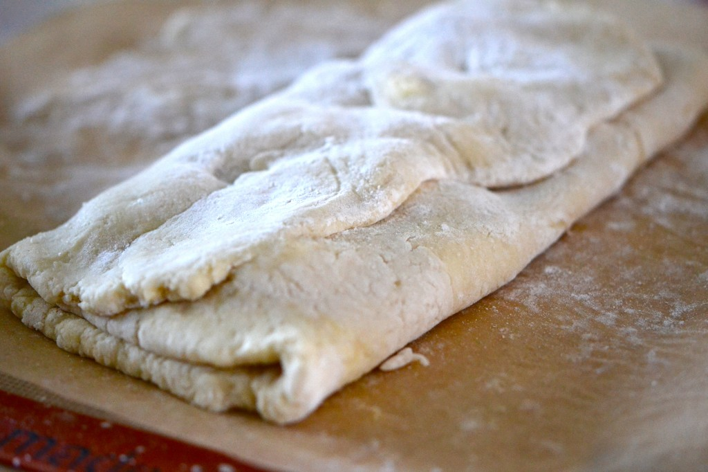 Dough being folded on brown surface