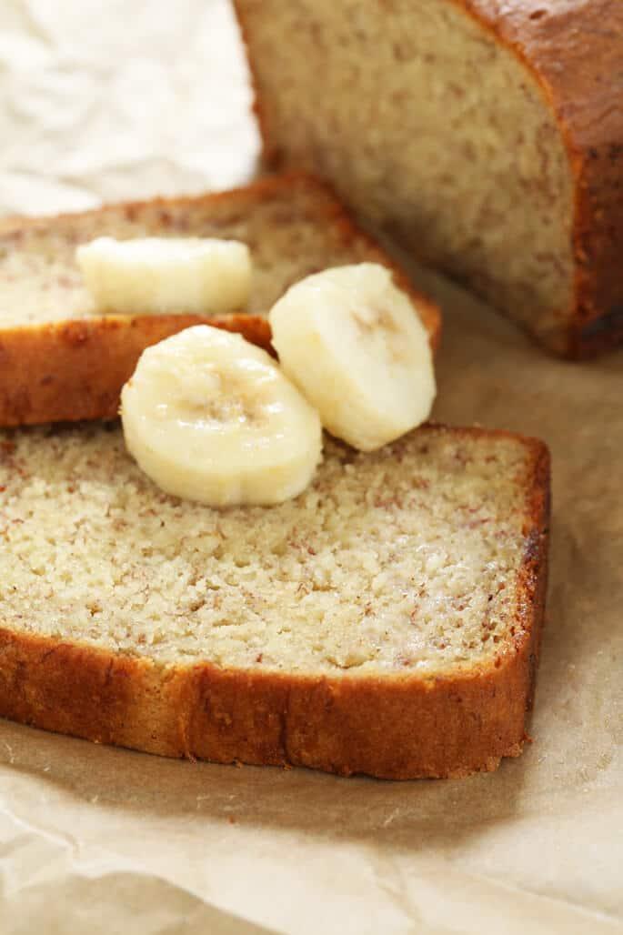 Closeup of a slice of gluten free banana bread with fresh bananas