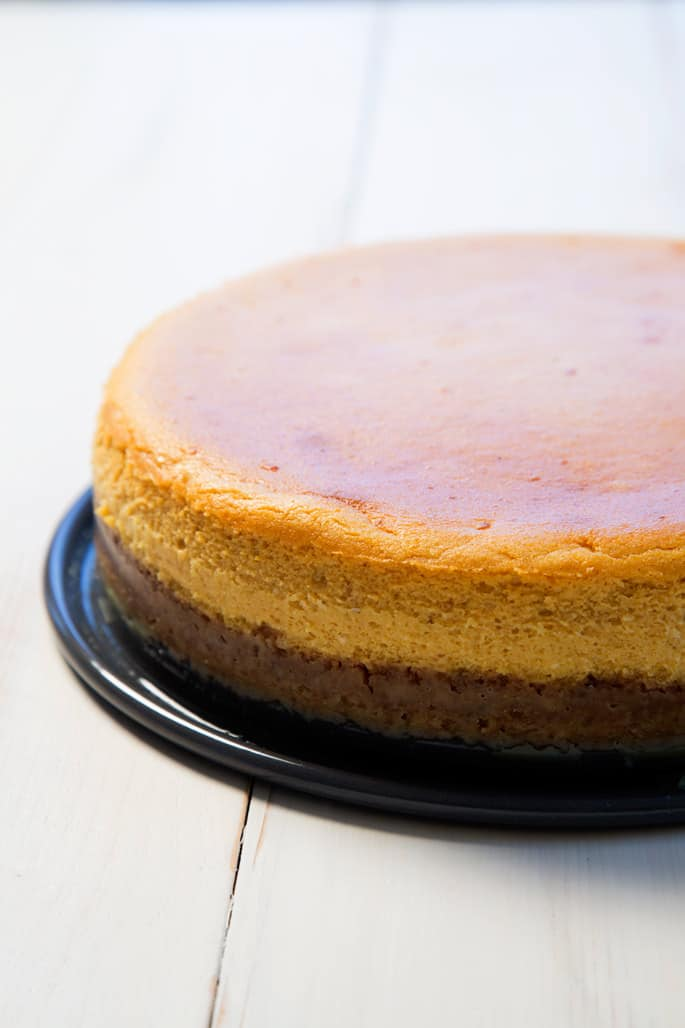 A close up of the side view of pumpkin cheesecake on black platter