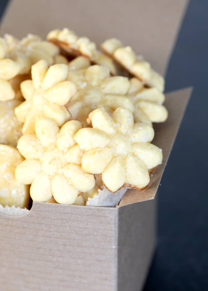 A close up of a box of gluten free butter cookies in a flower shape.