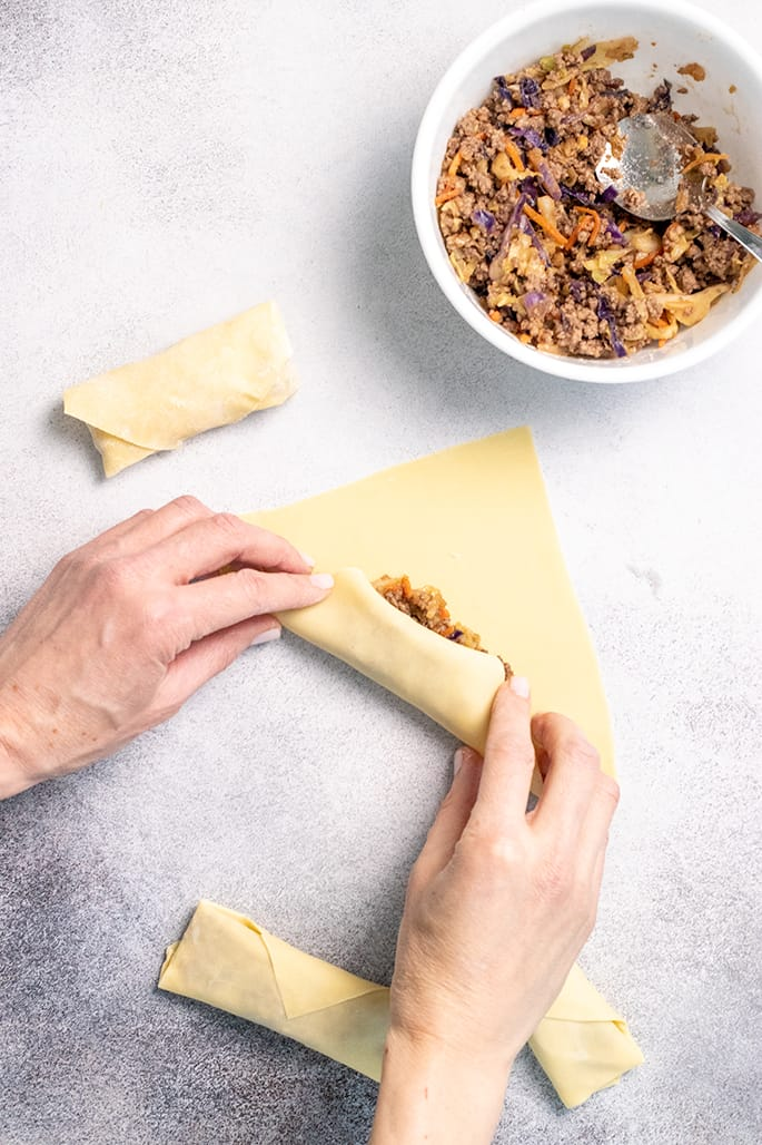 Overhead image of hands folding egg roll wrapper over filling with bowl of filling and more shaped egg rolls
