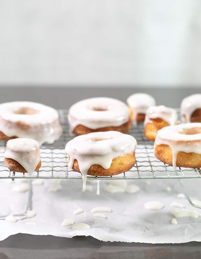 Donuts with white glaze on a rack
