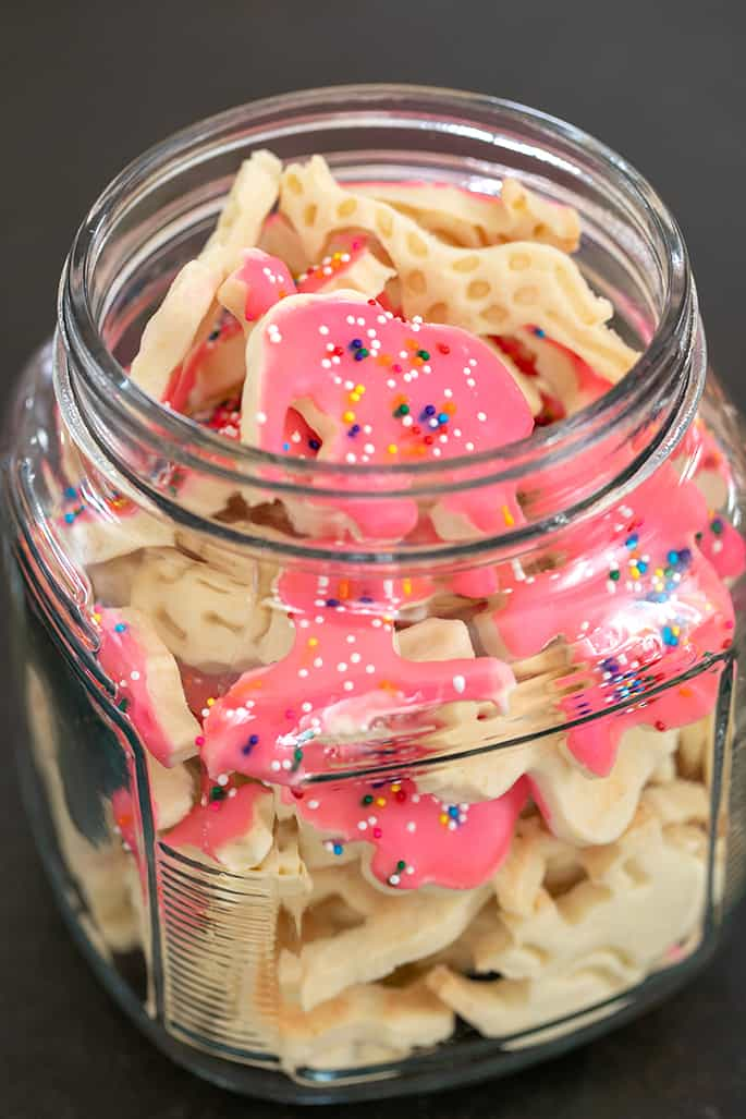 Glass jar filled with animal crackers some with frosting and nonpareils