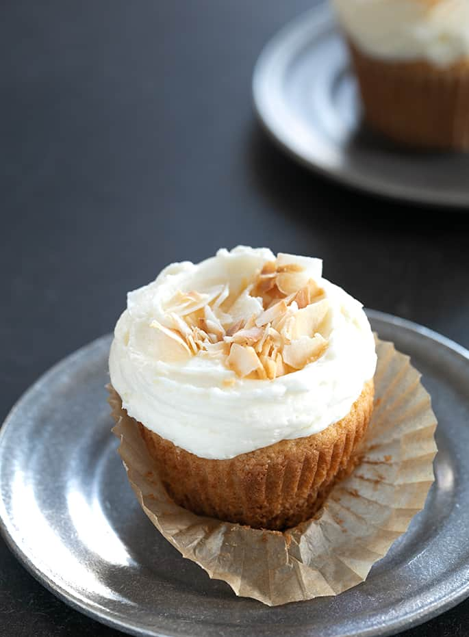 A closeup of a coconut cupcake with frosting and coconut on a small plate
