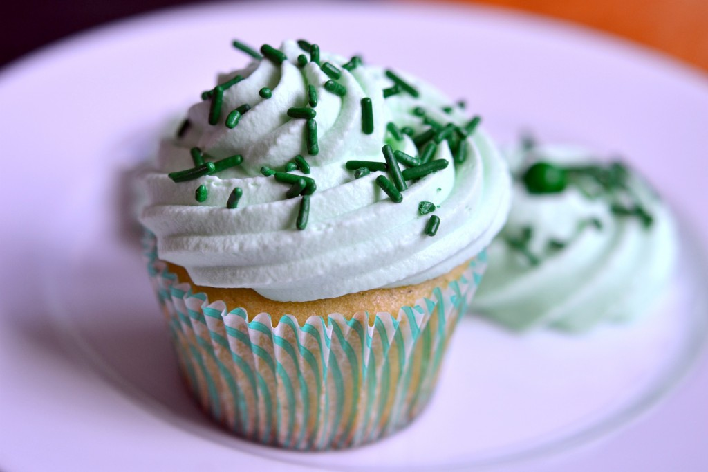 A close up of a Shamrock Shake Cupcake on purple plate