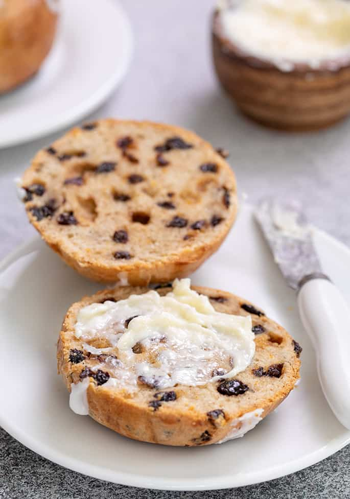 Hot cross bun split in half with butter and butter knife on small white plate
