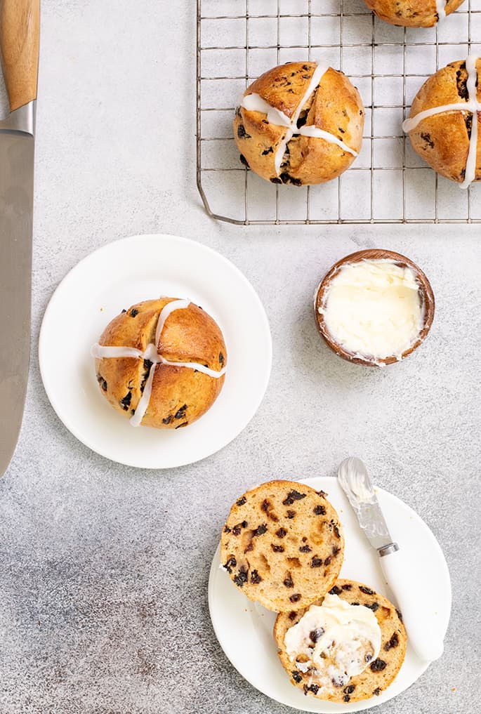 Overhead image of large knife, hot cross buns on wire rack, on small plate, and on small plate cut in half with butter