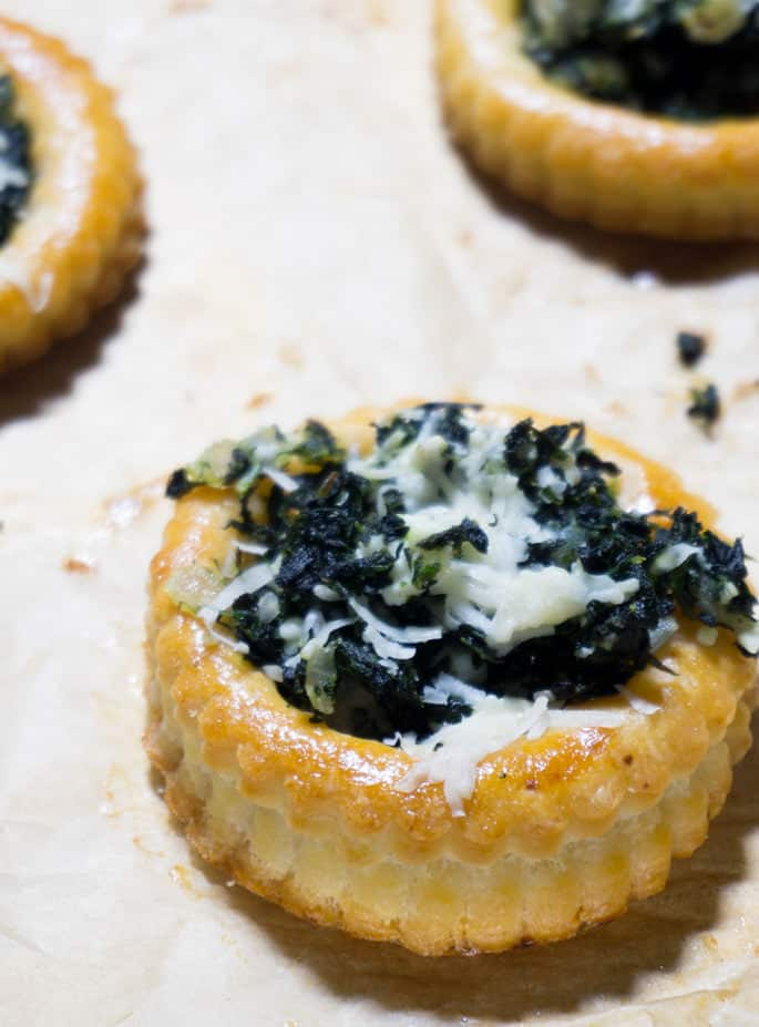 A close up overhead view of a spinach puff pastry on white surface