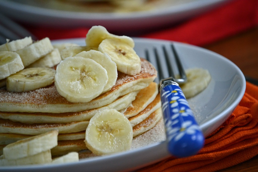 A stack of pancakes with bananas on white plate