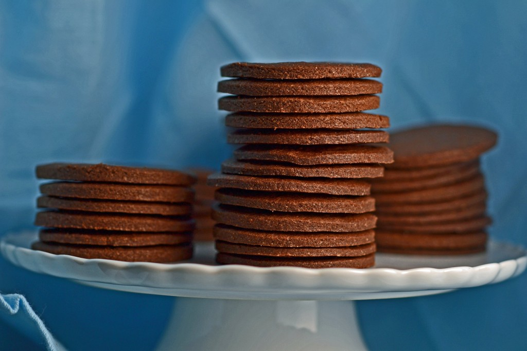 A close up of a white cake plate with stacks of chocolate wafer cookies