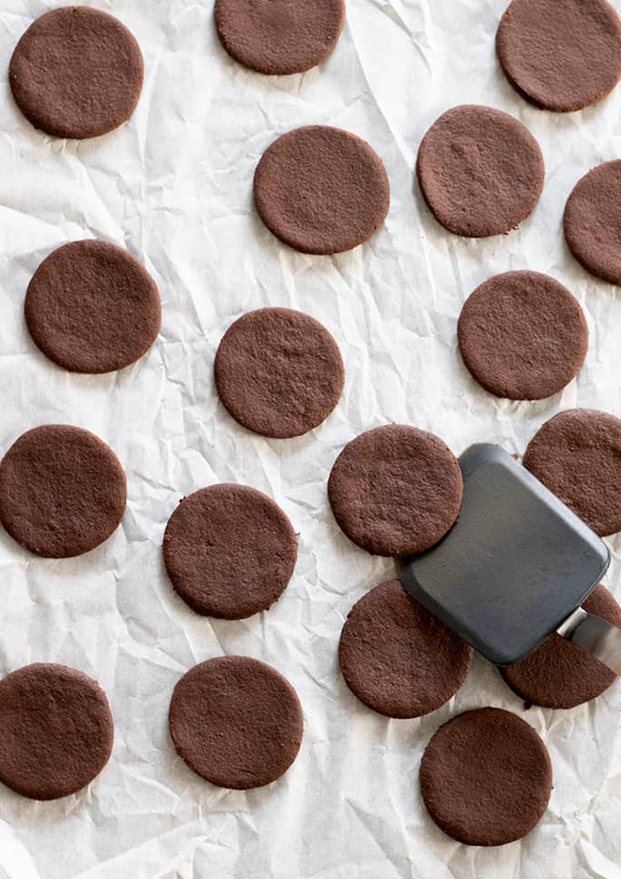 Baked gluten free thin mints cookies being taken off tray.