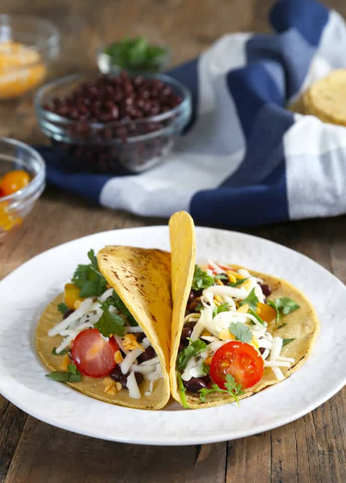Two fresh corn tortillas with tomatoes, beans, cheese, and parsley
