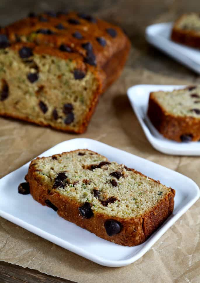 Two slices of gluten free chocolate chip zucchini bread each on a plate.