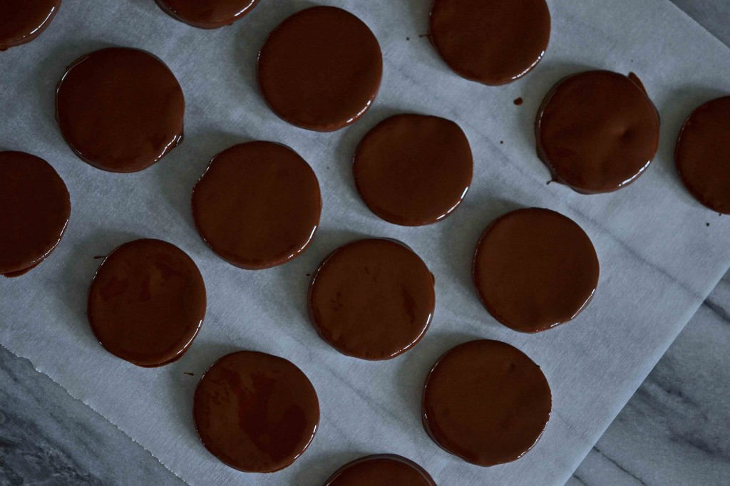Chocolate covered cookies on white surface