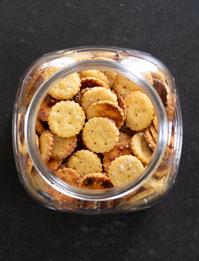 Overhead image of gluten free Parmesan crackers in a large jar