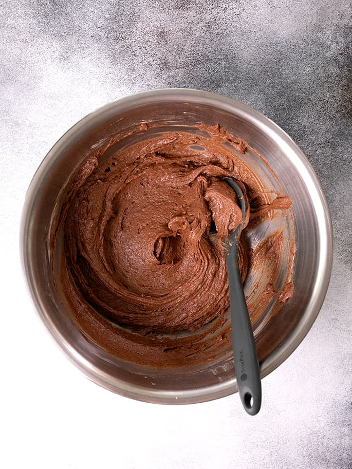 Milk chocolate cupcakes batter in a bowl with a spoon