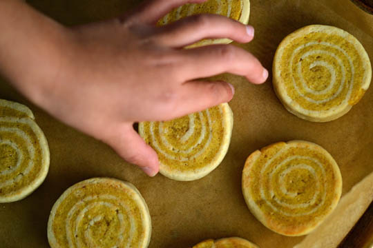 Person going to grab a pumpkin pinwheel cookie