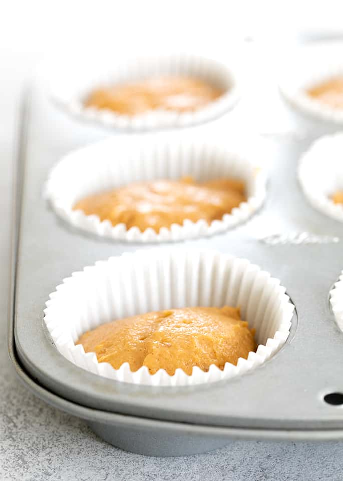 Pumpkin cupcake batter in muffin tin with white liners