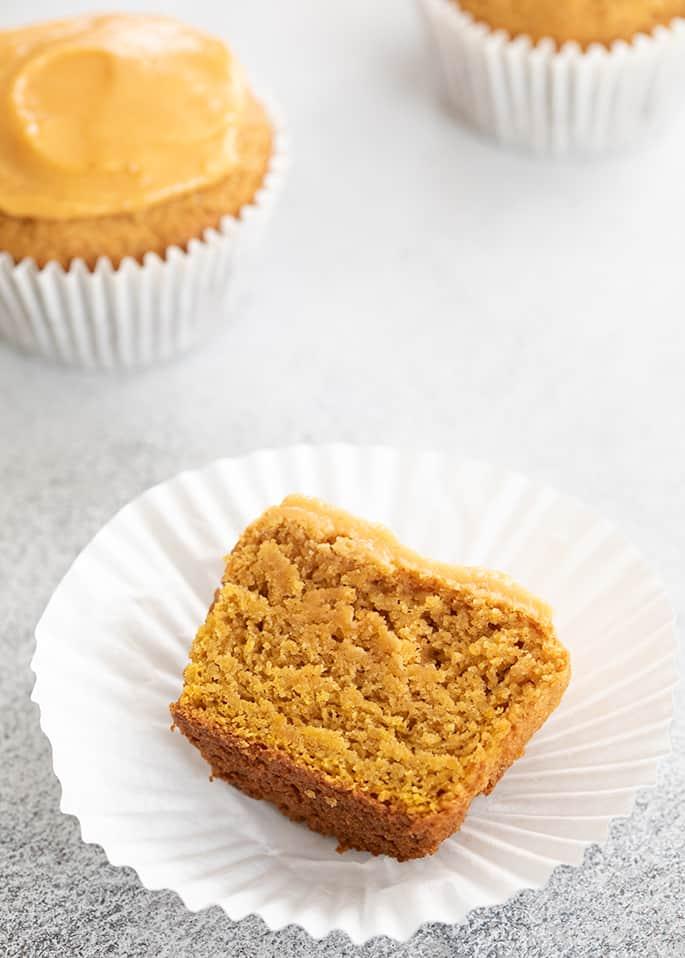 Pumpkin cupcake with icing cut in half