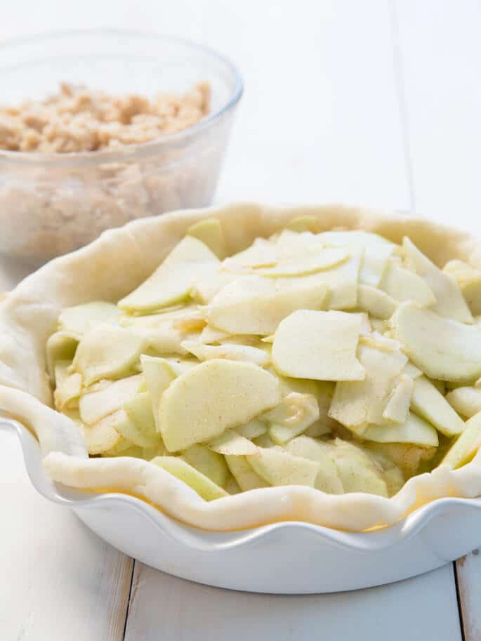 A close up of pie crust with apples and cinnamon inside a white baking tray