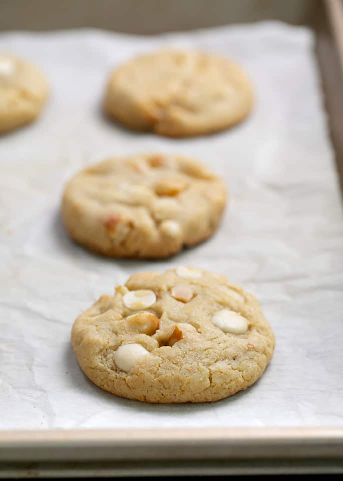 White chocolate macadamia cookies baked on white paper on tray
