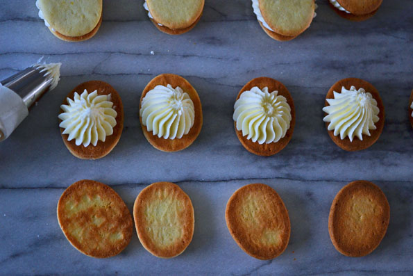 Vanilla Wafer Sandwich Cookies being frosted