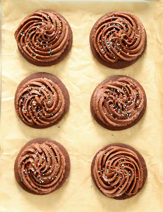Overhead view of 6 chocolate cutout cookies with nonpariels on beige paper