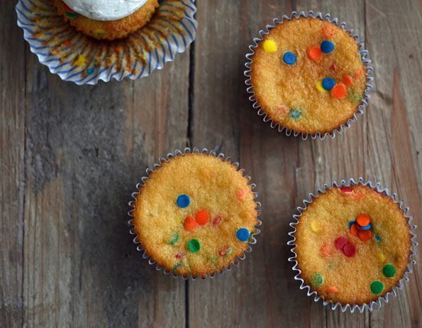 Overhead view of funfetti cupcakes on wooden surface
