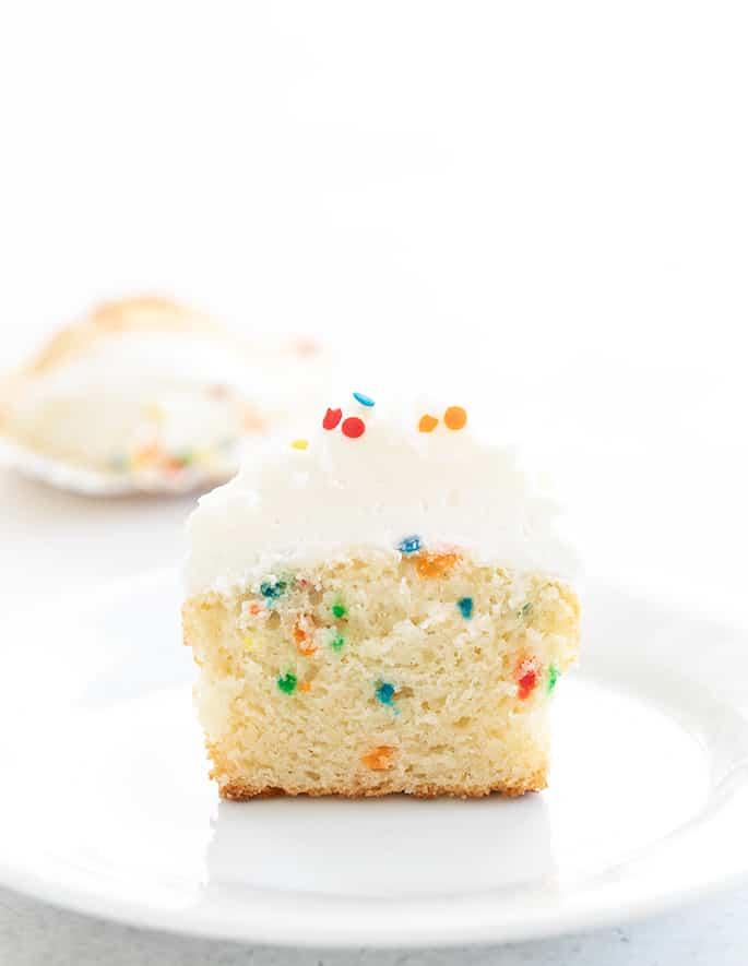 Gluten free Funfetti cupcake on a plate sliced in half