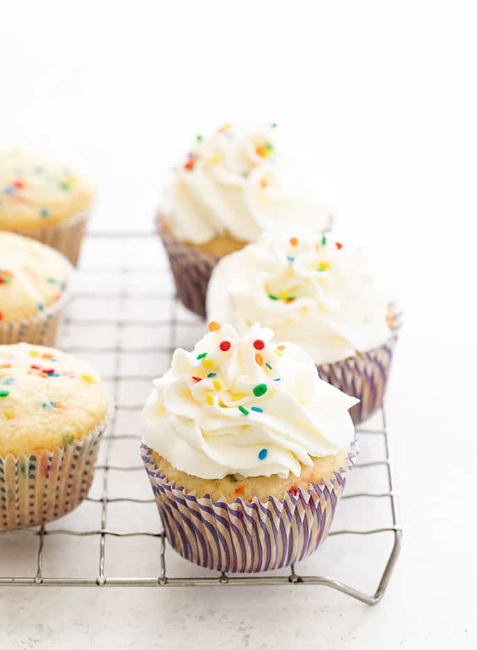 Gluten free funfetti cupcakes frosted on a wire rack
