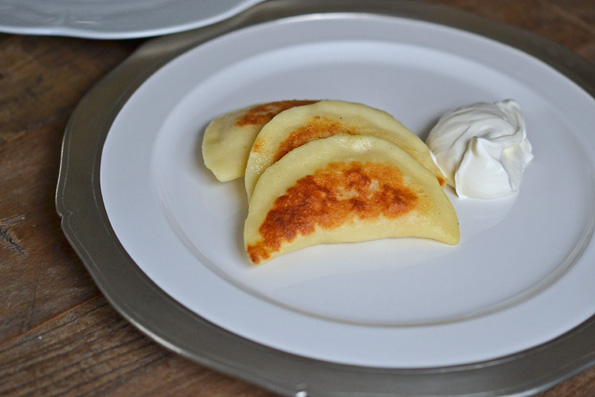 Close up of 3 pierogis on a white plate