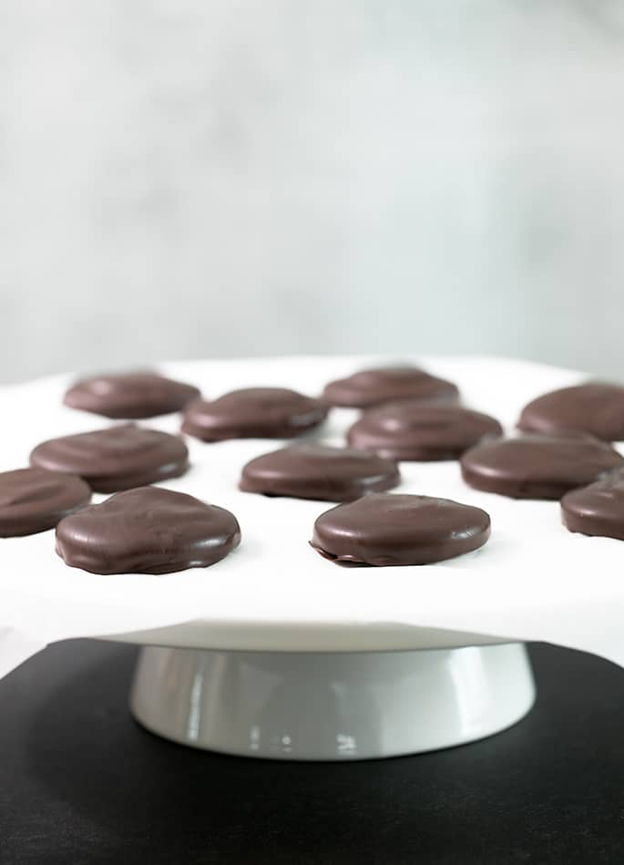 A cake plate with tagalong cookies on white paper