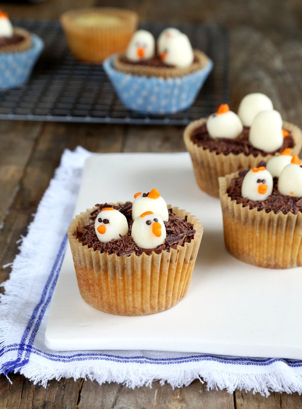 Cupcakes in brown wrappers with 3 molded chocolate chick heads on each, all on white surface
