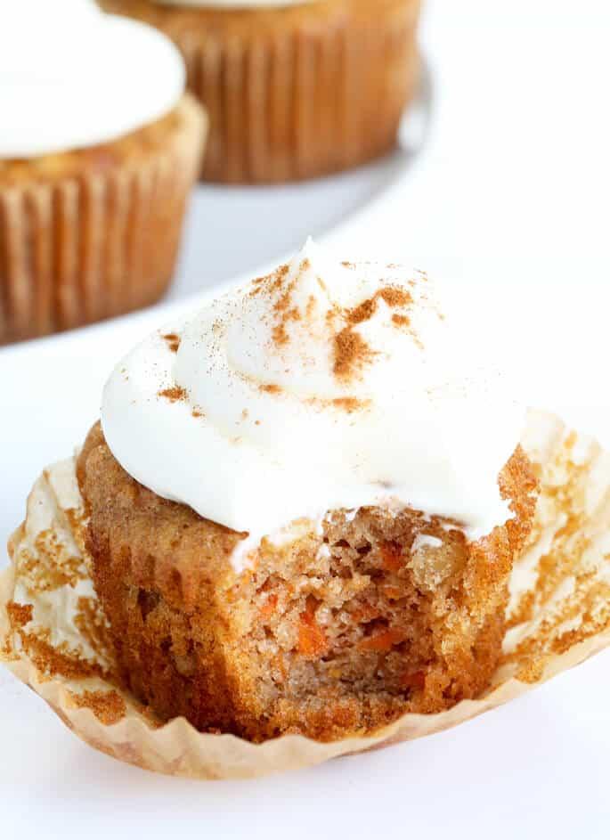 A carrot cake cupcake with a bite taken