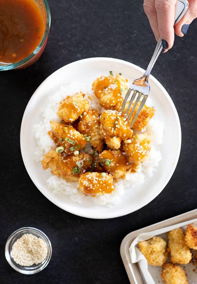 Gluten free sesame chicken overhead being served and eaten.