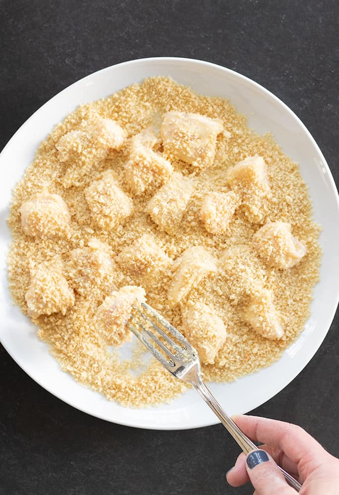 Gluten free sesame chicken raw and being tossed in bread crumbs.