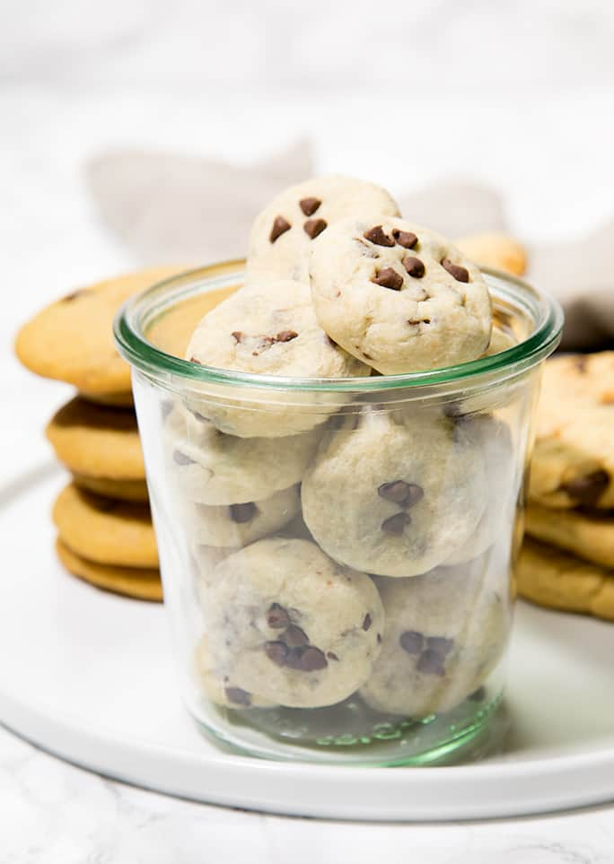 A close up of a jar of chocolate chip cookies with stacks of chocolate chip cookies on white surface in back