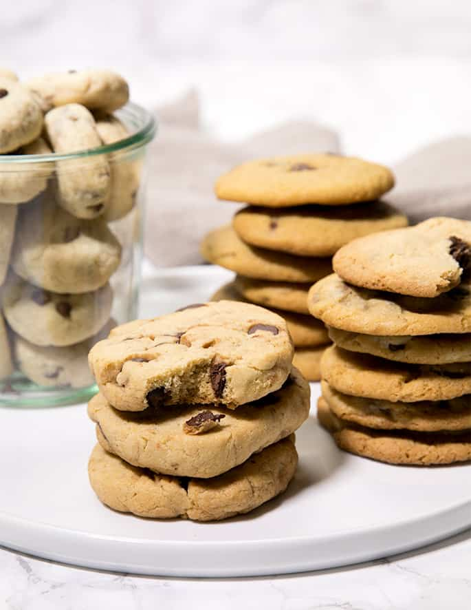 3 stacks of chocolate chip cookies on white surface with jar of chocolate chip cookies in background