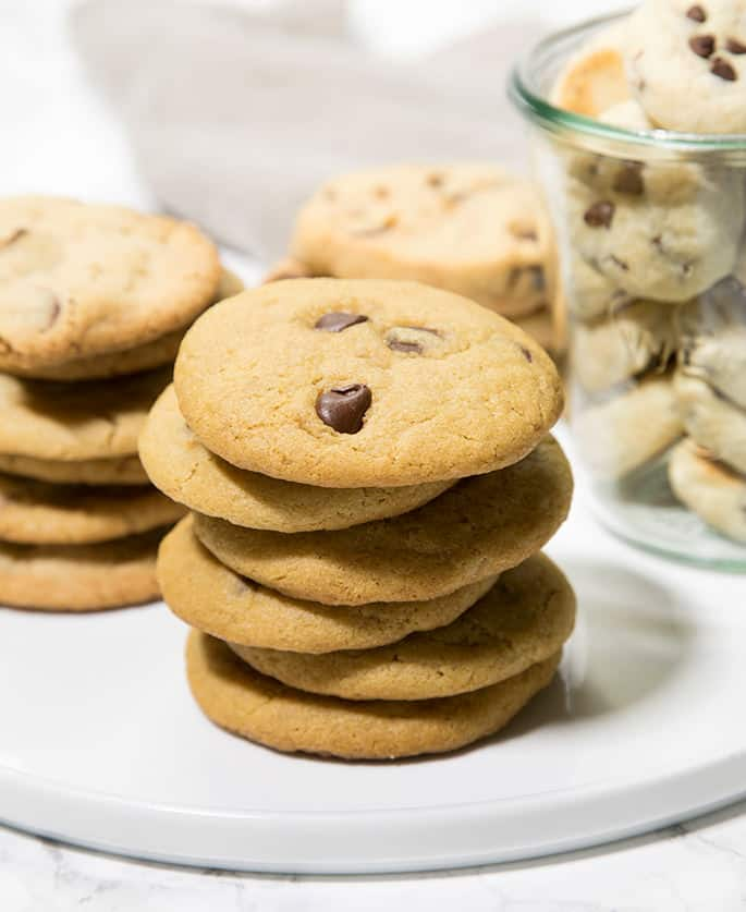 Different arrangement of 3 stacks of chocolate chip cookies on white surface with jar of cookies in back