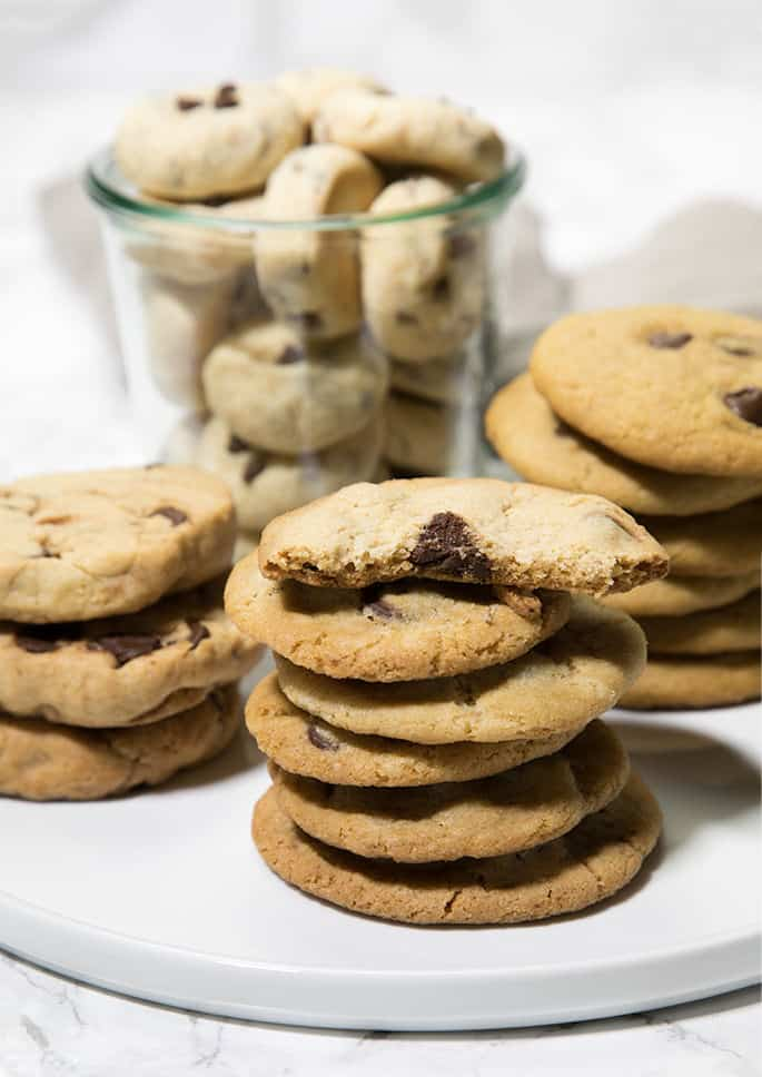 3 stacks of chocolate chip cookies and view of inside of one cookie with jar of chocolate chip cookies in back