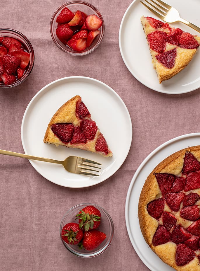 Overhead image of strawberries in 3 small glass bowls, a slice of cake with strawberries on top on a white plate and the rest of the cake on a white serving platter