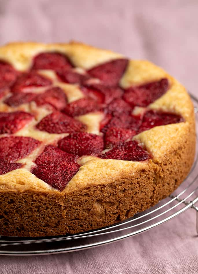 Side view of baked roasted strawberry cake out of pan cooling on a wire rack on a plum colored cloth