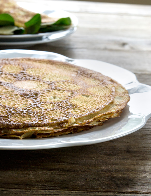 Stack of buckwheat crepes on white plate